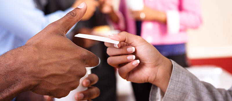 A man's hand is seen on the left receiving a business card from the female's hand on the right.