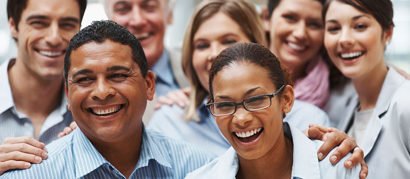 Group of diverse people dressed in business casual clothing, smiling.