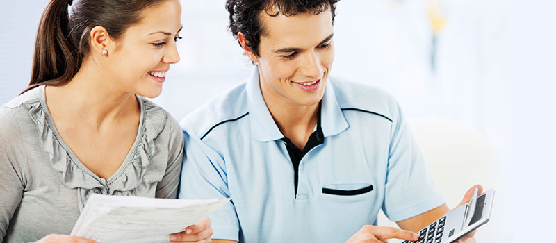 Woman and man looking at form and calculator happily.